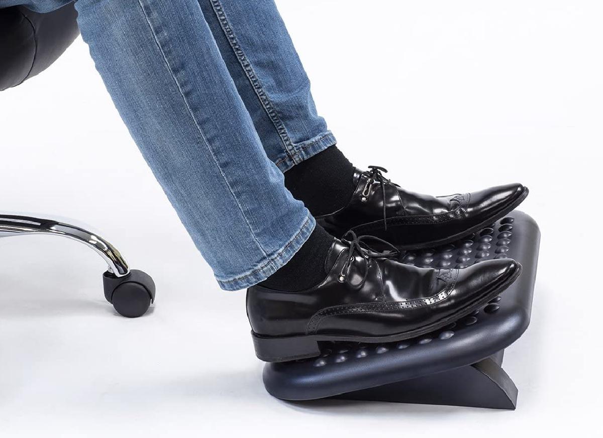 Adjustable Ergonomic Footrest with man's feet on it