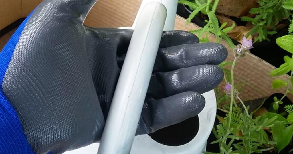 gloved hand holding watering can