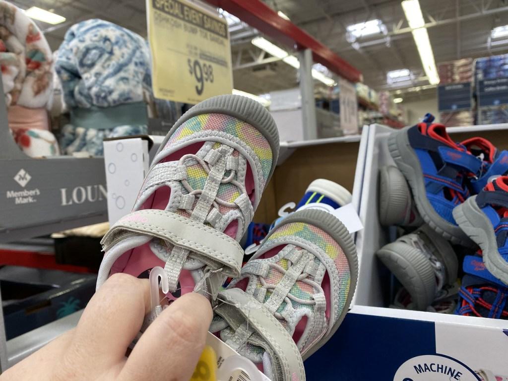 Hand holding up Osh Kosh Tie Dye Sandals