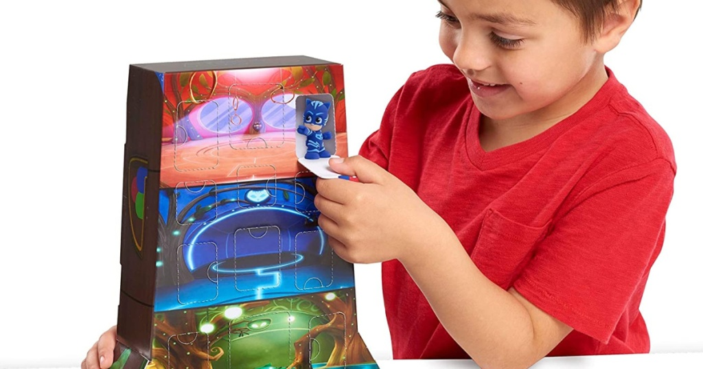 boy playing with a PJ masks playset
