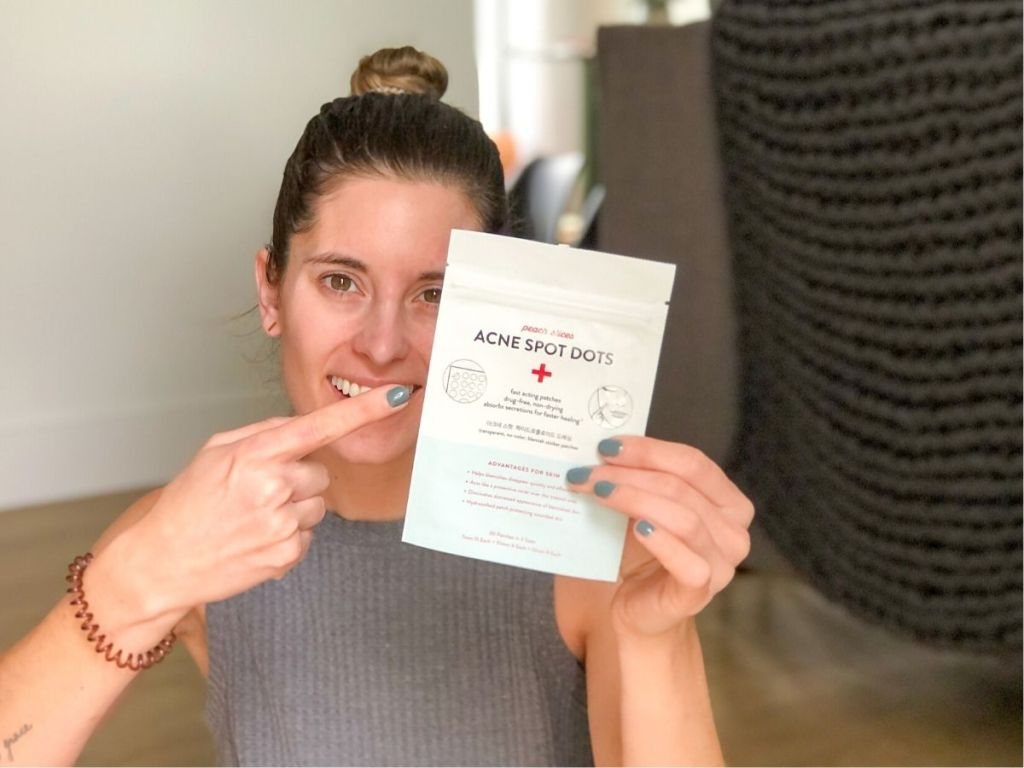 woman holding acne spot dots package