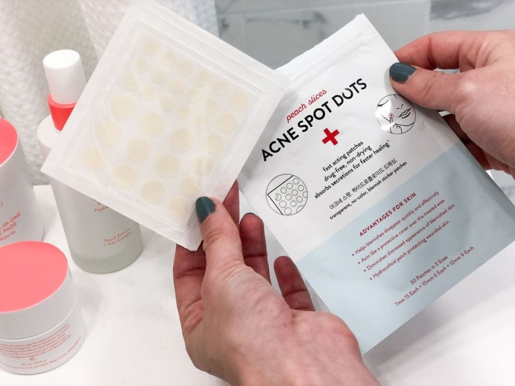 hand holding acne spots dots package and sheet