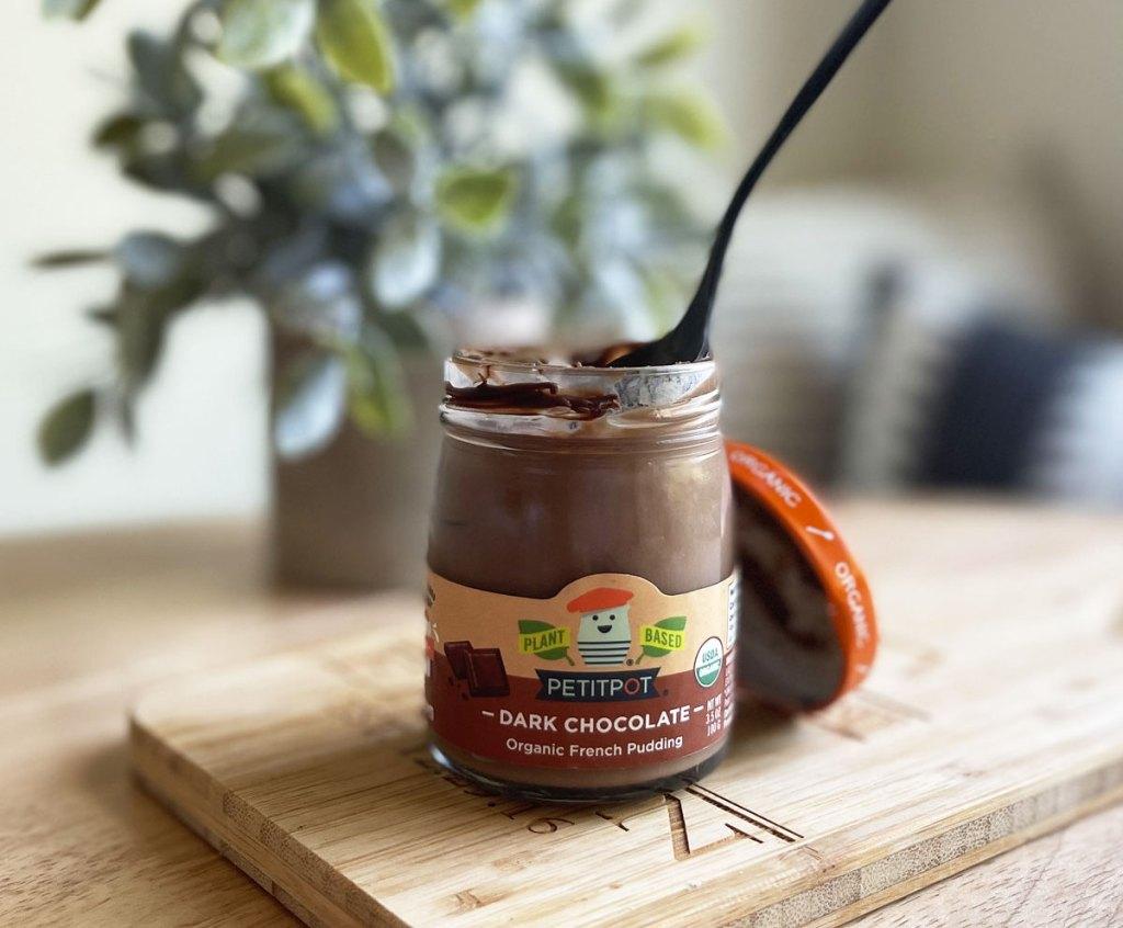 opened jar of petitpop chocolate pudding on wood cutting board