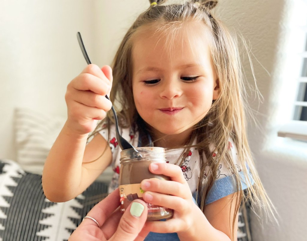 little girl taking spoonful of chocolate pudding