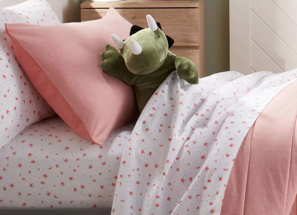 bed with sheets, pillow and dinosaur plush