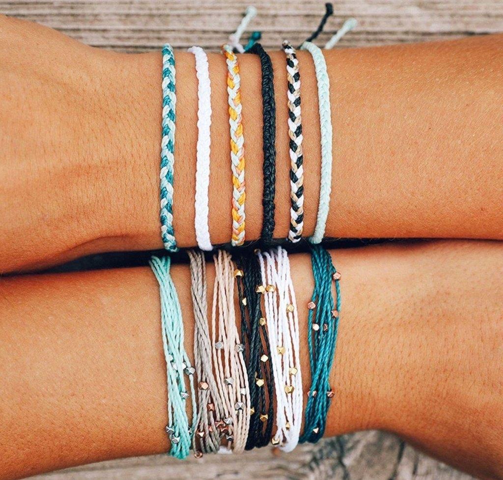 pura vida bracelets on arms