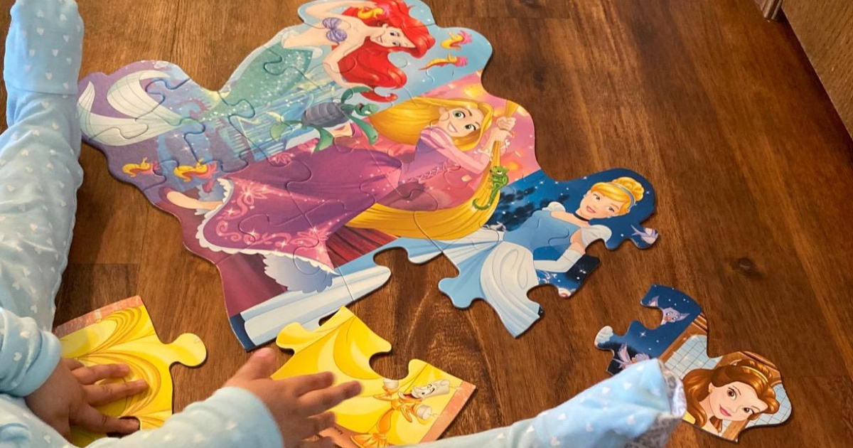 child putting together a disney princess floor puzzle