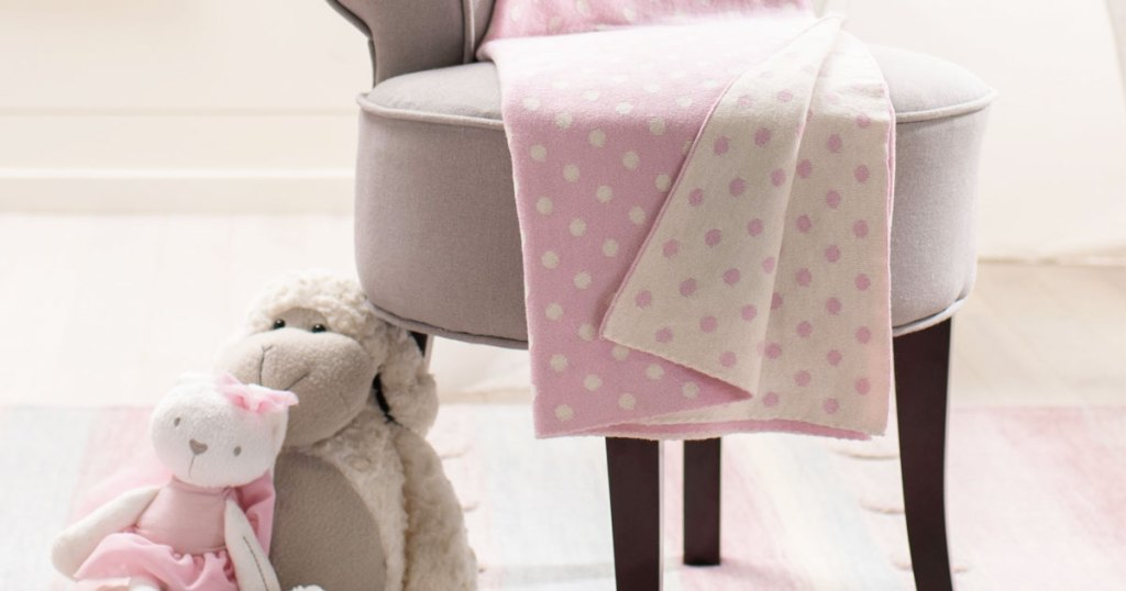 dotted baby blanket on chair next to stuffed animals