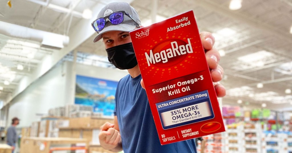 man holding up and pointing at a box of megared kill oil