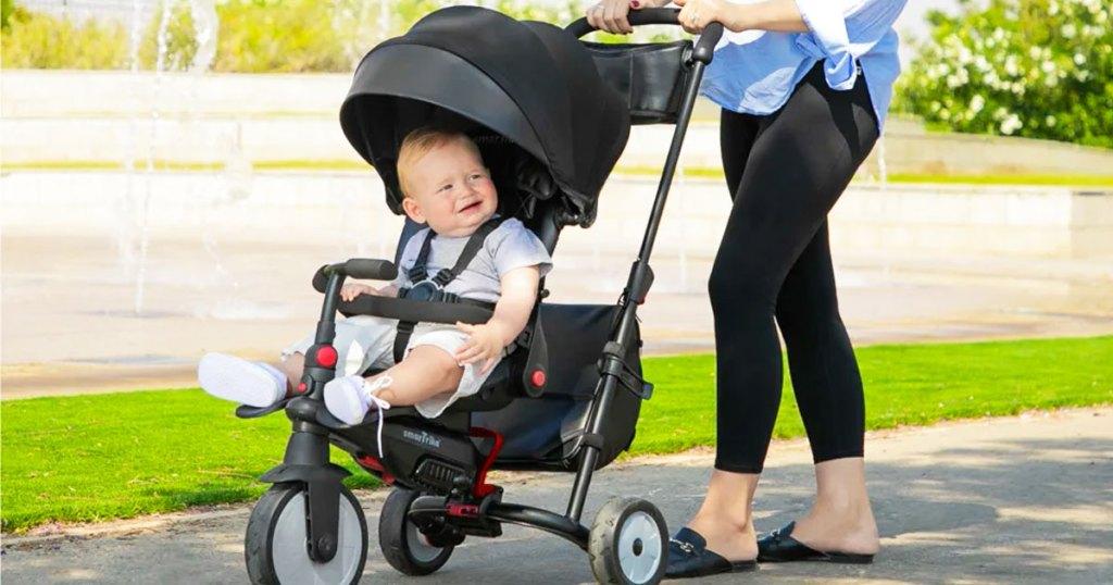 woman pushing baby in black stroller trike