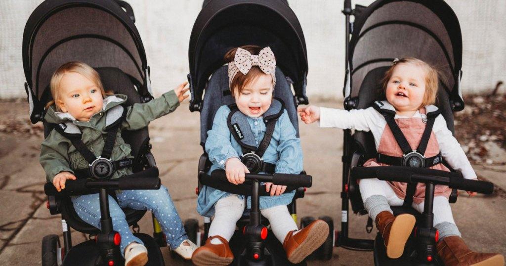 three toddlers in trike strollers