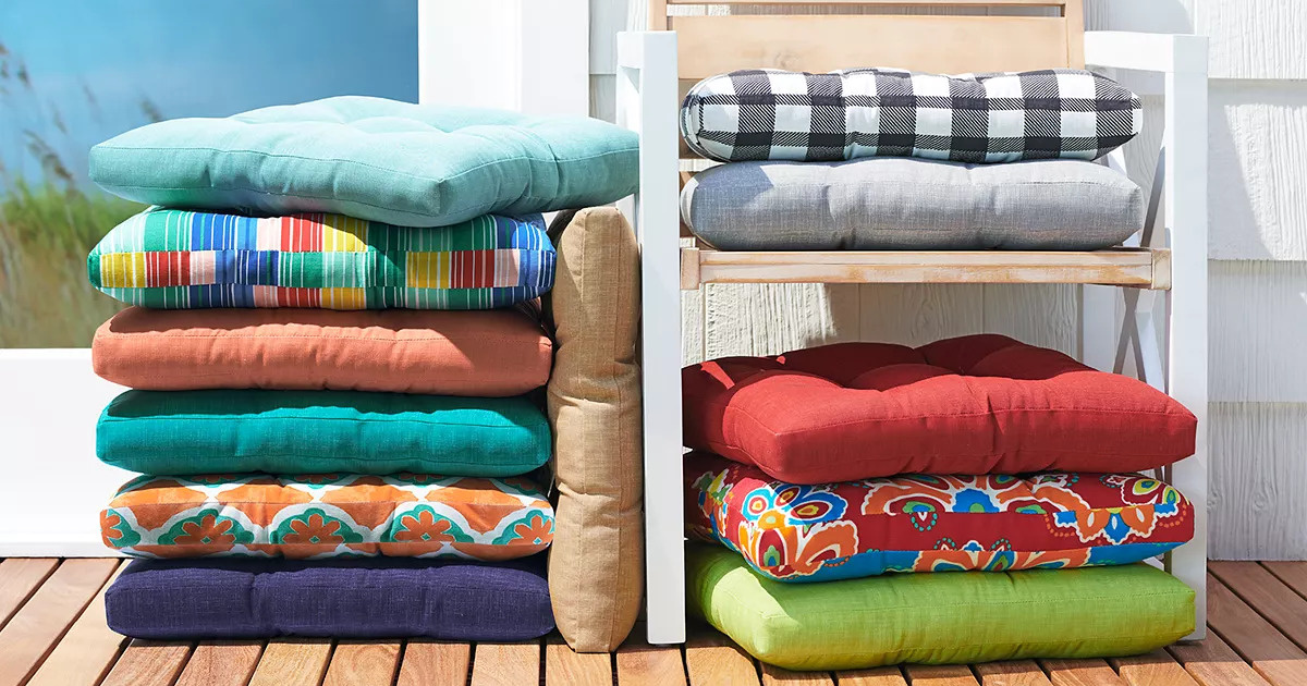 stacks of colorful outdoor pillows on and next to a chair on a deck