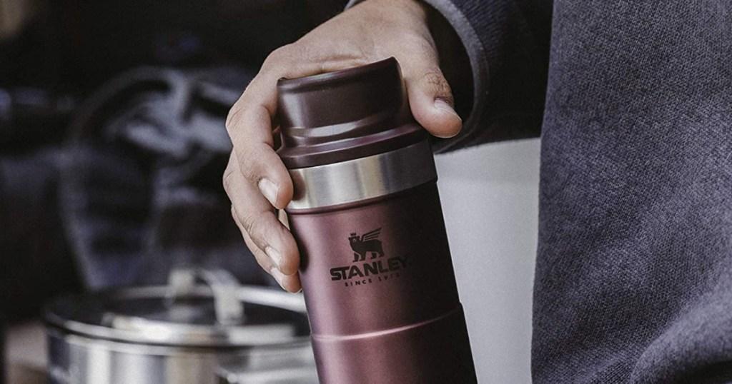 Man holding Stanley Travel Mug