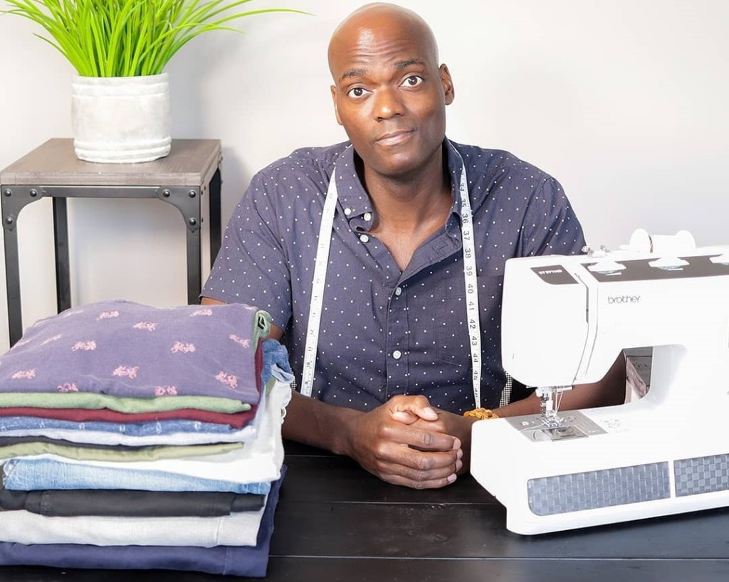 man sitting next to a sewing machine