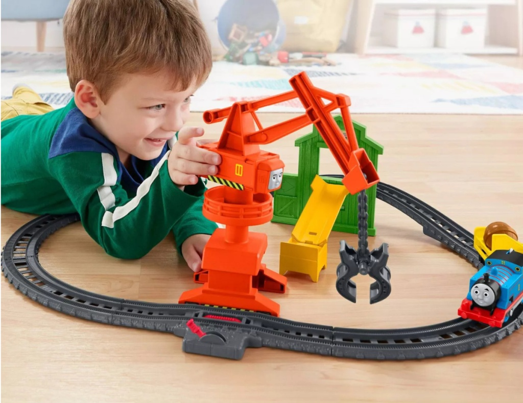 Boy playing with train set