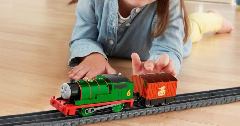 girl playing with a toy train