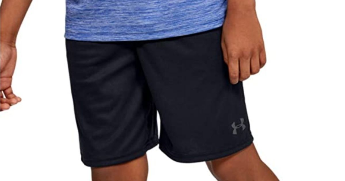 child wearing Under Armour Boys Athletic Shorts in black with blue shirt