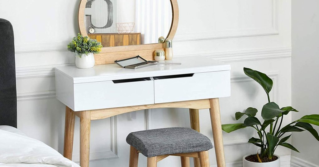 white makeup vanity with round wood mirror and grey stool