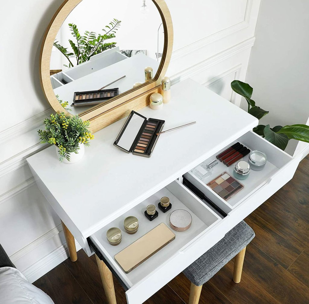 white makeup vanity with opened drawers showing products inside