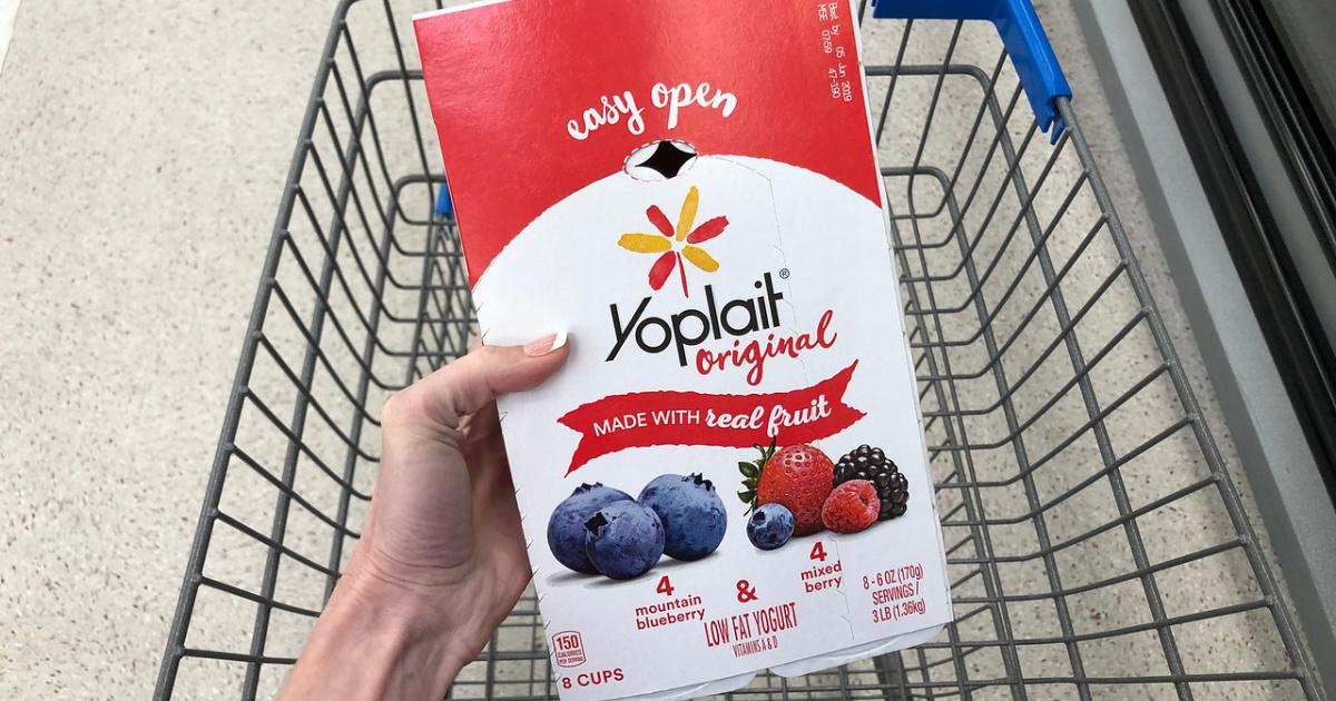 hand holding a package of yoplait yogurt above a walmart shopping cart