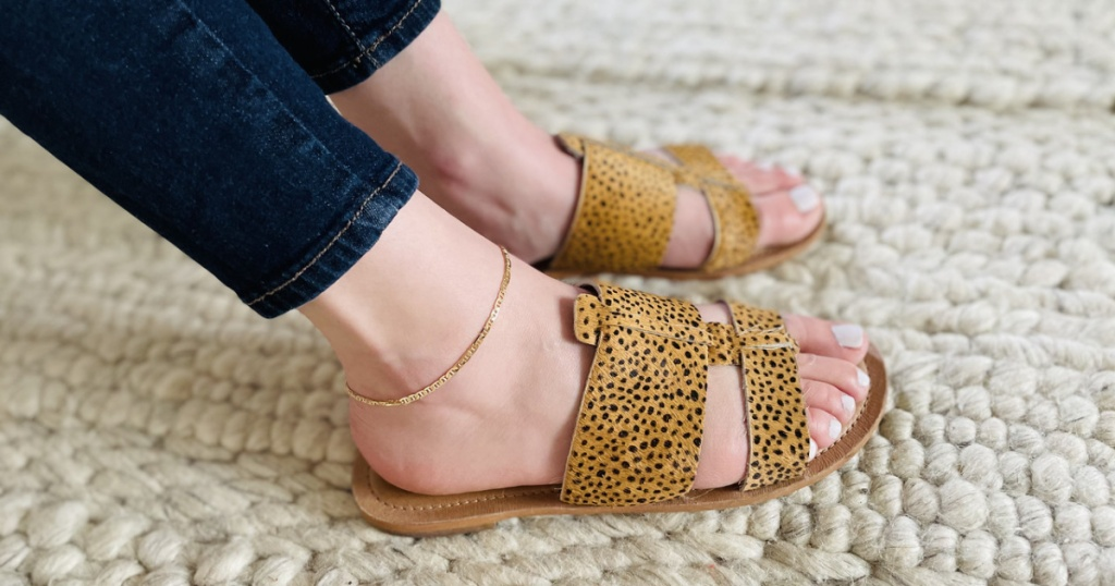 woman wearing skinny jeans, a gold anklet and leopard print sandals
