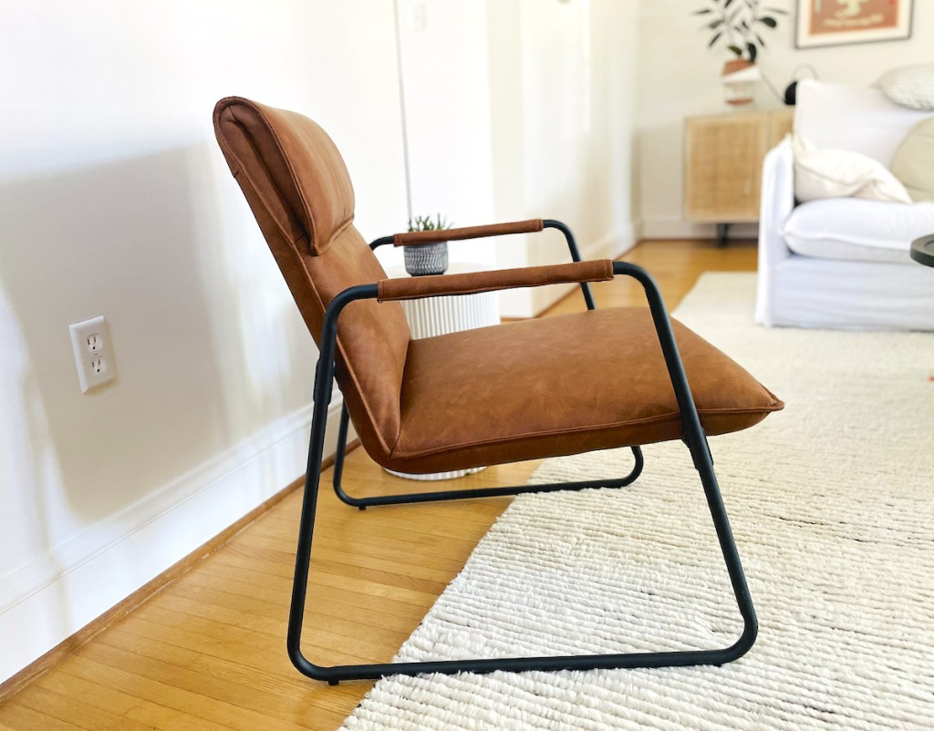 close up of brown leather mid century modern accent chair in living room