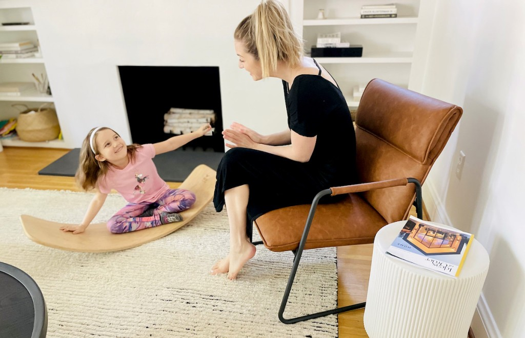 girl playing on balance board next to woman on leather sling chair