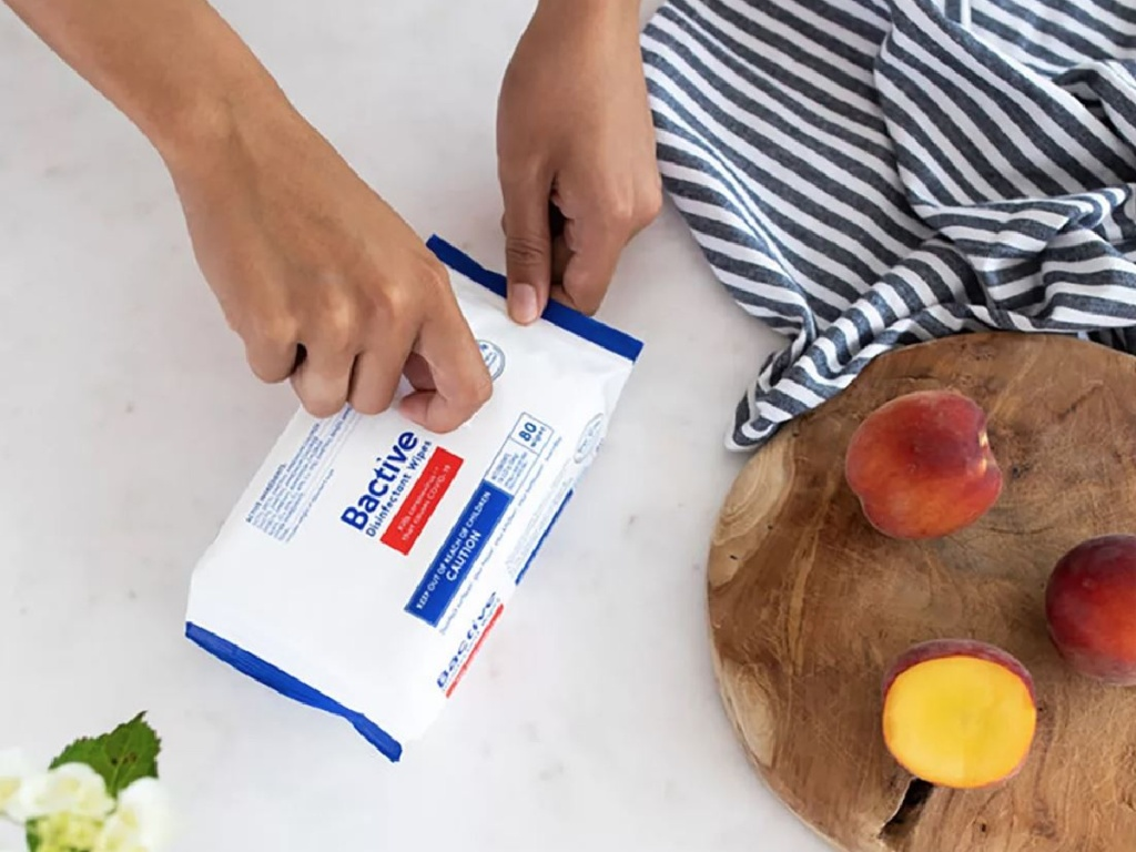 hand opening package of wipes by food counter