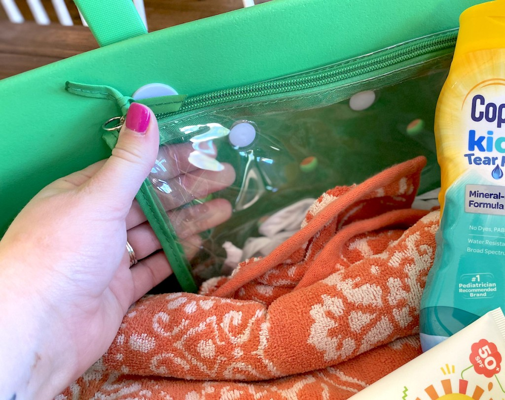 hand pulling clear bag off side of green tote