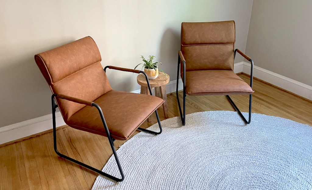 two modern leather chairs sitting on jute rug