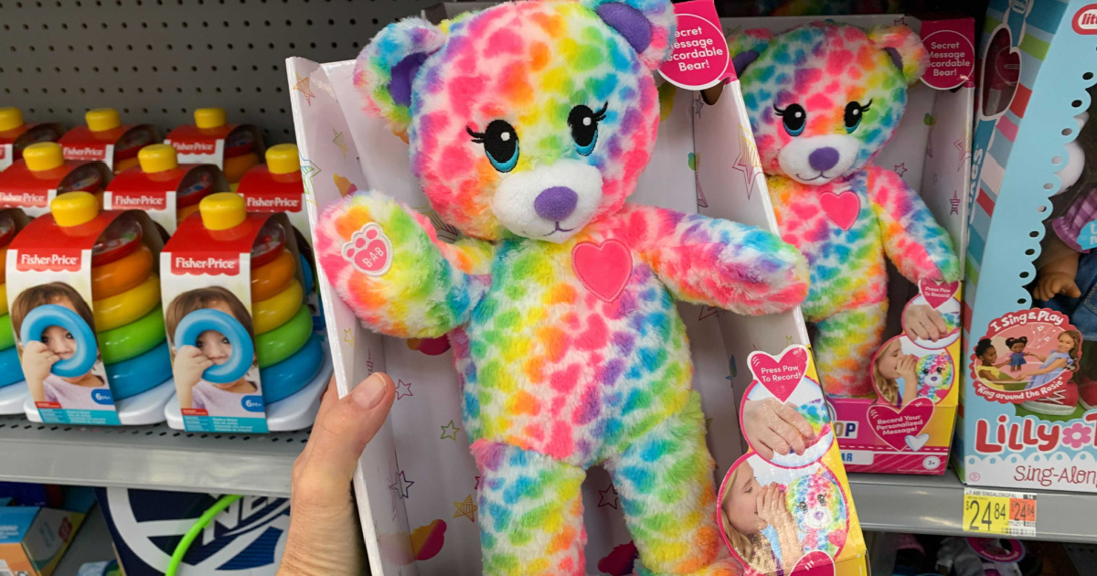hand holding up a colorful bear in front of a store display