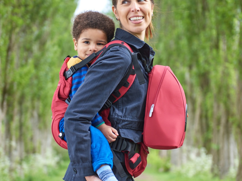 woman carrying child in a back pack outside