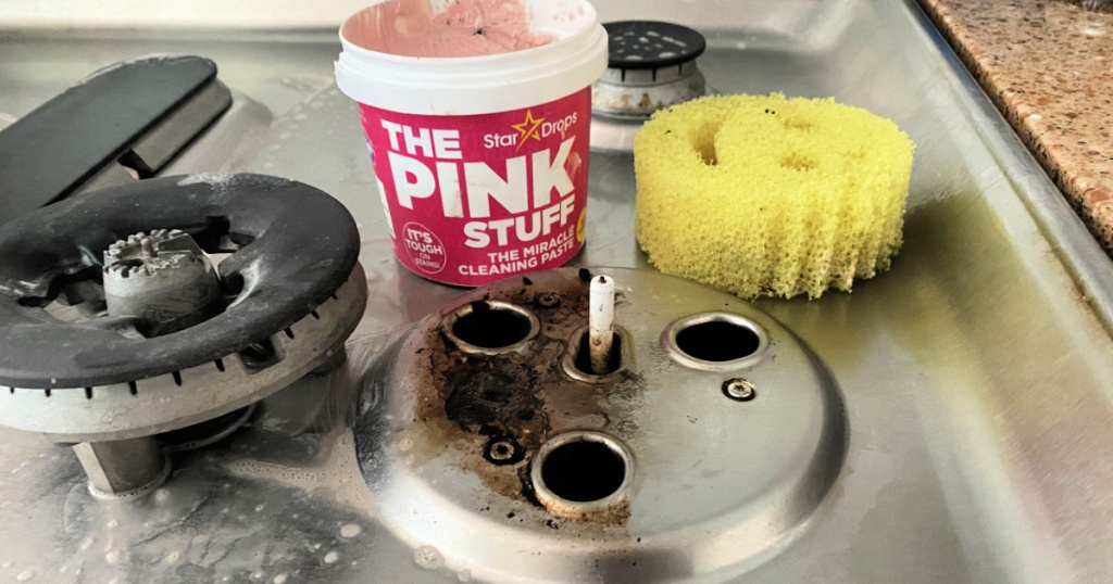 cleaning the stove top with the pink cleaner
