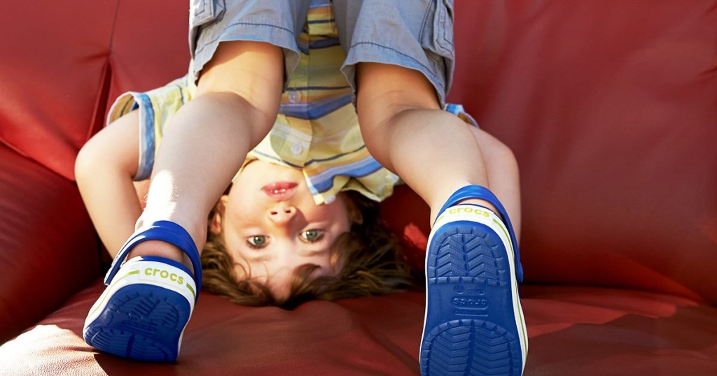 kid sitting upside down on red couch
