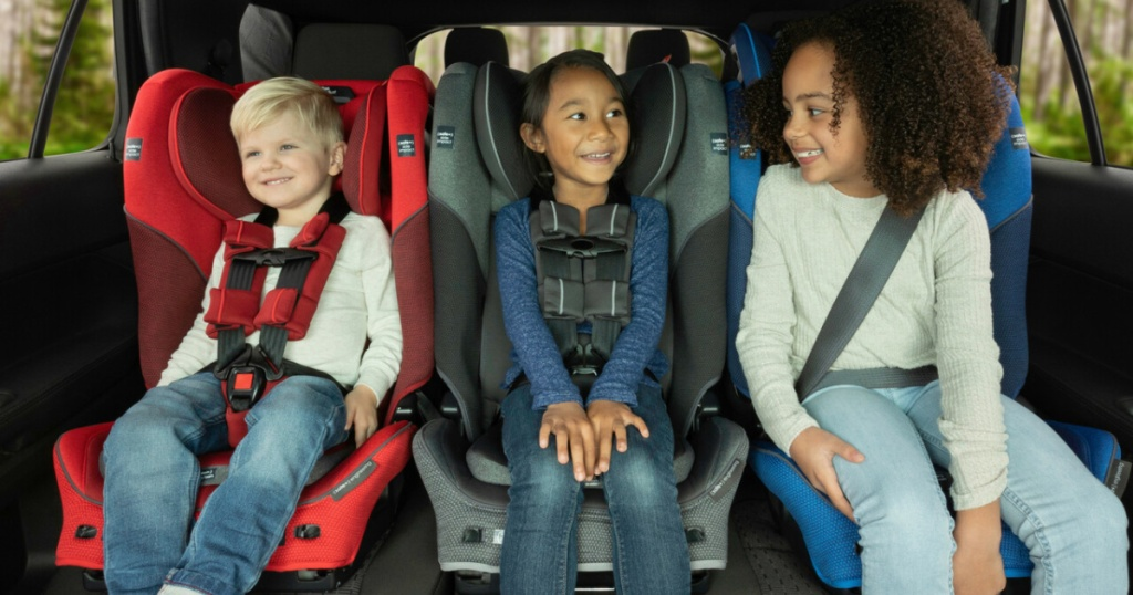 three children in backseat of car in carseats