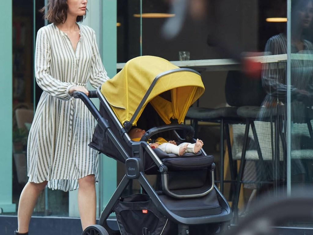woman pushing stroller near stores