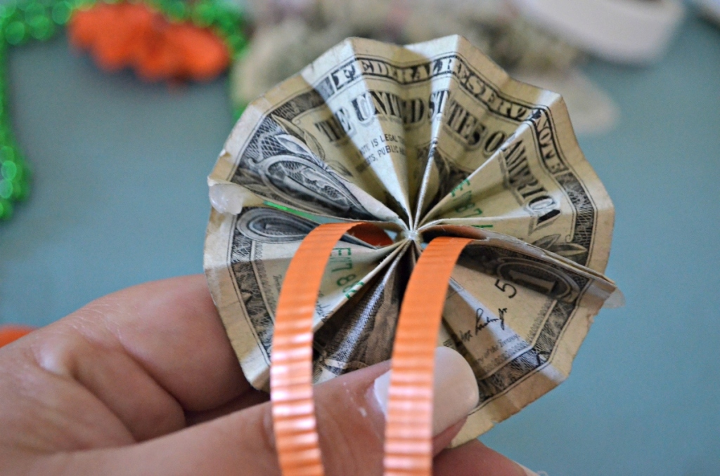 holding a rosette made from a folded dollar bill