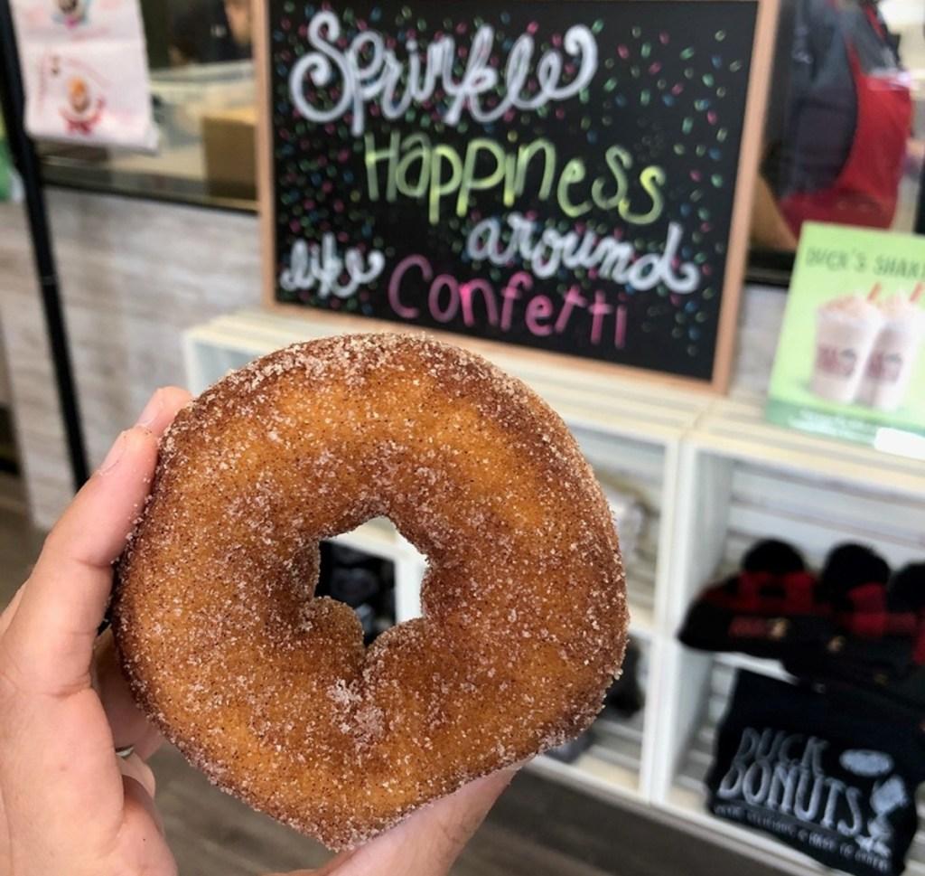 holding a cinnamon donut