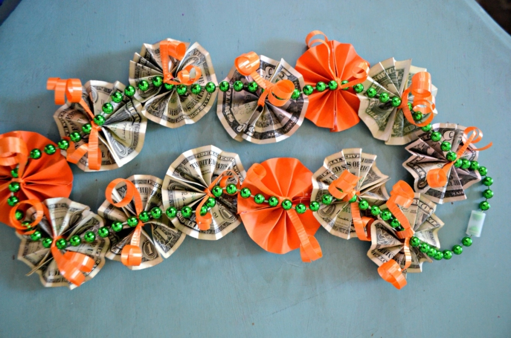 graduation lei with orange paper flowers and folded money