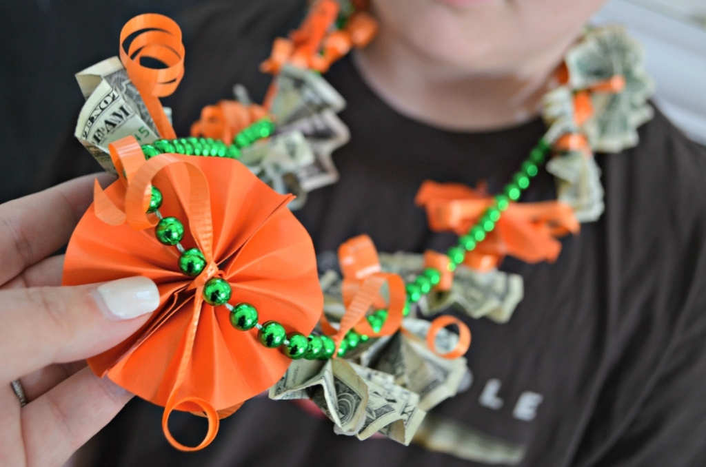 wearing a graduation lei made of orange paper and dollar bills