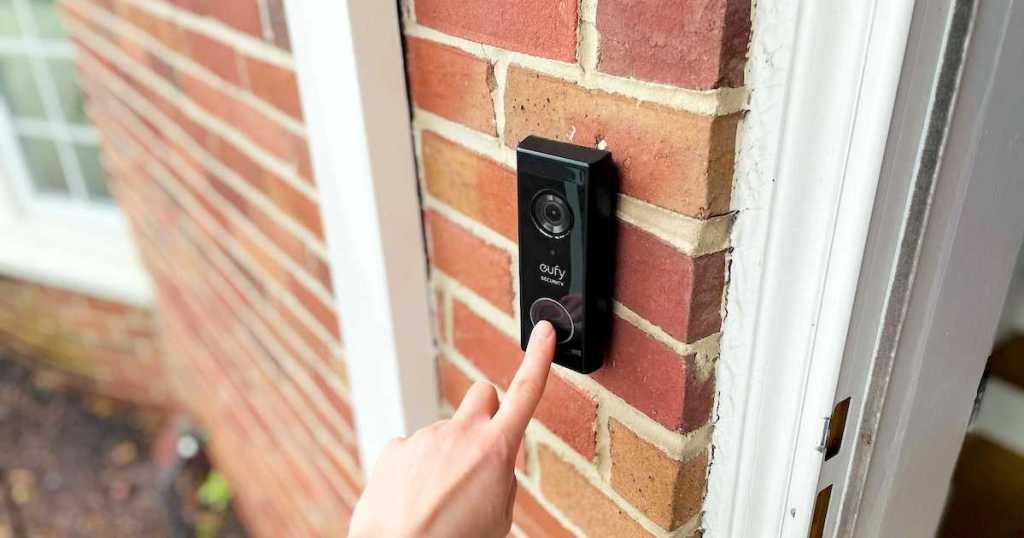 hand pushing on black eufy camera doorbell