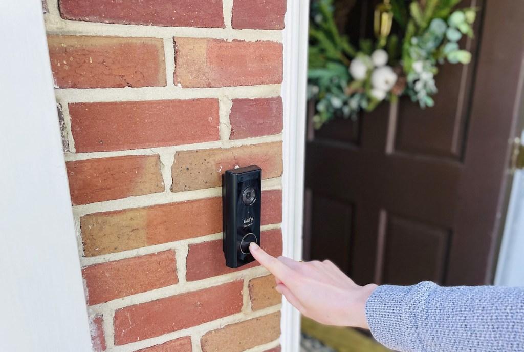 finger pushing on eufy video doorbell