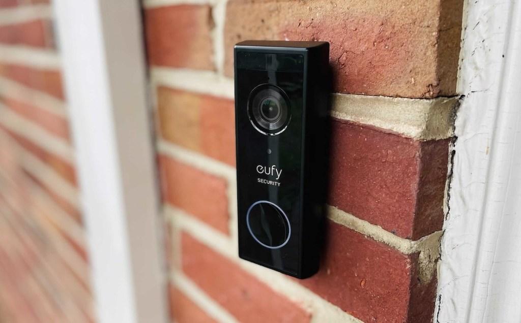 close up of black eufy video doorbell on brick house