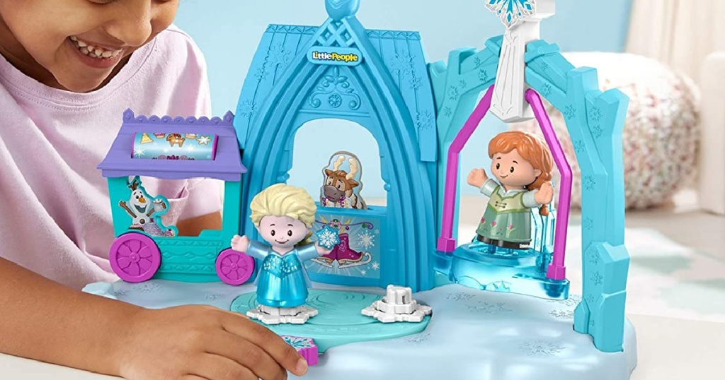 young girl playing with disney frozen playset