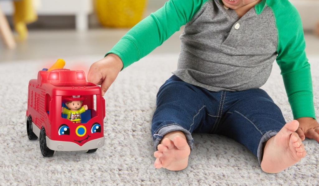 boy playing with fisher price firetruck