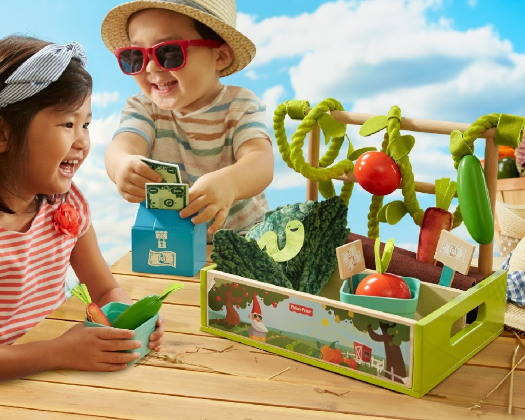 toddlers playing with fisher price market stand toy