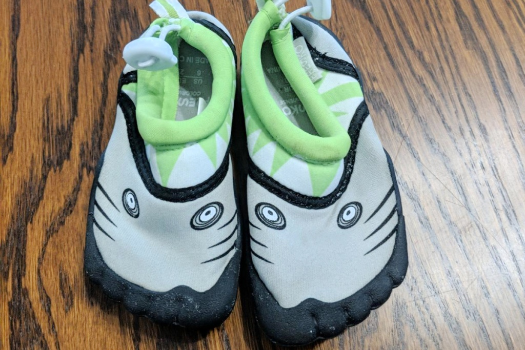 kids green and black fresko water shoes on wood table