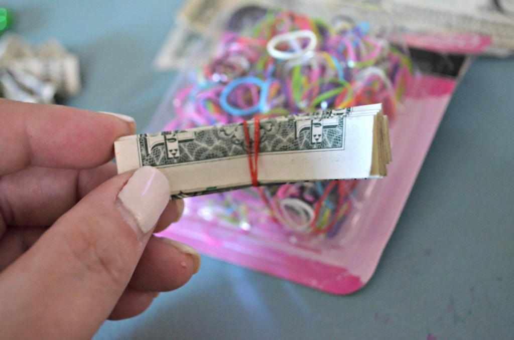 holding a folded dollar bill wrapped in a rubber band