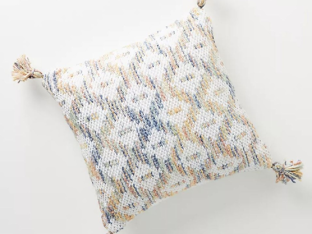 pillow with tassels and light colors woven through it