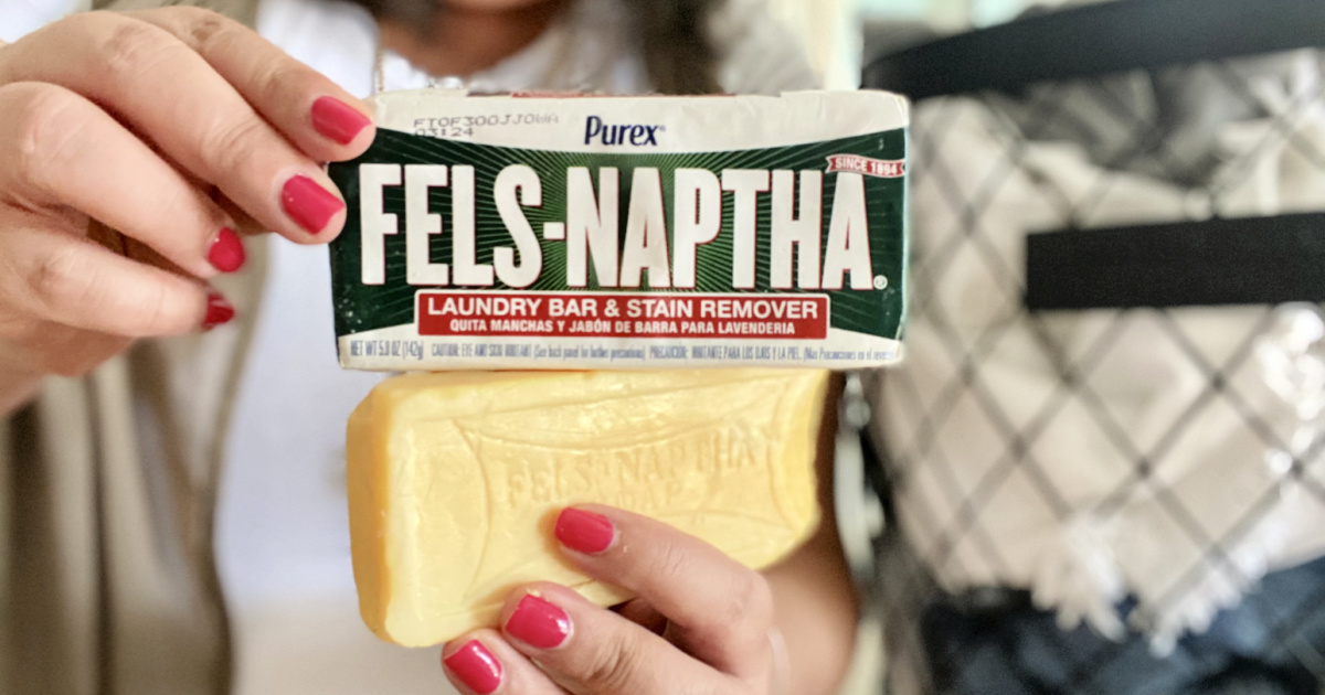 holding up two bars of fels-naptha soap bars
